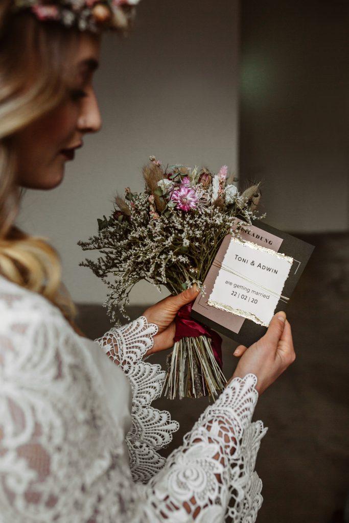 Braut hält Einladungskarte Hochzeitseinladung